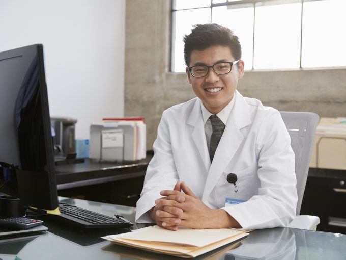 young asian male doctor sitting at desk portrait R7P8U6E
